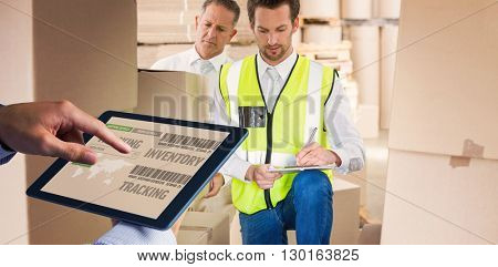 Man using tablet pc against delivery driver checking his list on clipboard