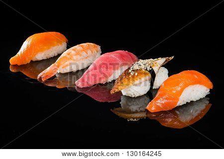 assortment of nigiri sushi on a dark background