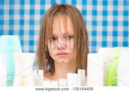 Sad girl is looking at various cosmetics in bathroom