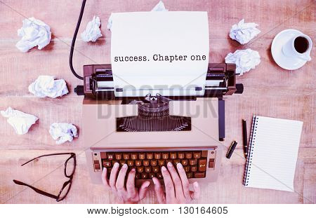 Success. Chapter one message on a white background against above view of old typewriter