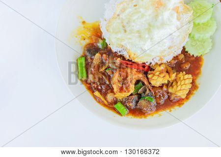 stir fried seafood in thai red curry paste with rice and fried egg Spicy Fried seafood Curry fried shrimps and cooked rice in white dish closeup on table