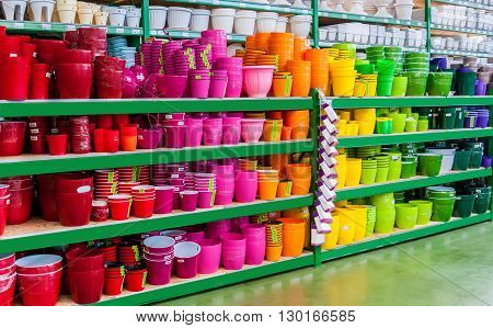 beautiful colorful flower pots on the shelves of a shop of garden household