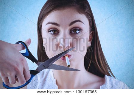 Woman cutting cigarette with scissors against blue background