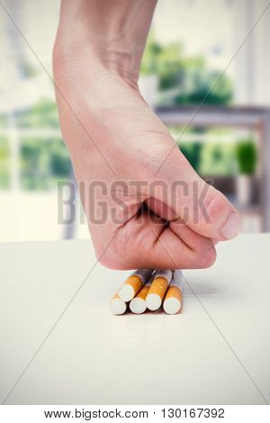 Composite image of hand squashing batch of cigarettes