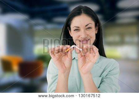 Smiling woman snapping cigarette in half against college