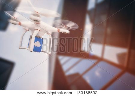 Digital image of a drone holding a cube against low angle view of skyscraper on a sunny day