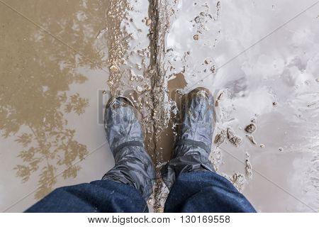 Photo with legs in the mud puddle in a shoe full of holes