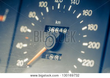 Automobile speedometer with orange arrow and white digits on dark background. Tinted image