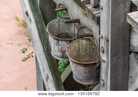 A photo with two rusty bucket on the wall