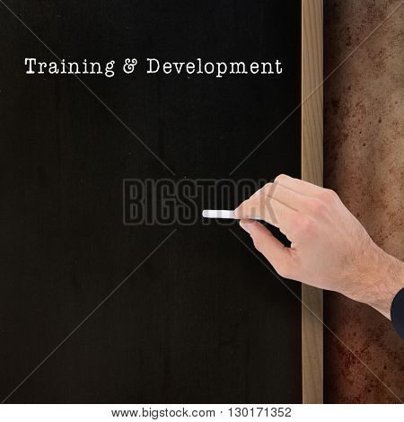 Hand of a businessman writing with a white chalk against blackboard on wall