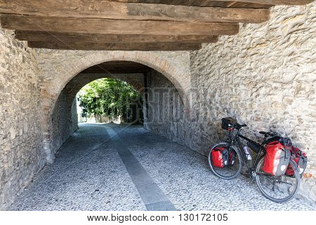 Montevecchia (Lecco Brianza Lombardy Italy): historic village a typical alley and a bicycle with black and red bags