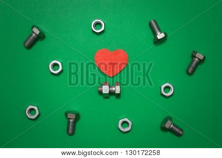 Red heart as love symbol and bolt with screw nut as symbols of life companions among other bolts and screw nuts on green background. Life companion searching metaphor