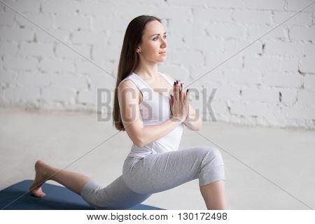 Attractive Young Woman Doing Ashwa Sanchalasana Pose In White Loft