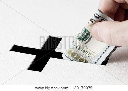 Hand of parishioner is inserting one hundred dollars into hole for donations in form of Christian cross on white background. Idea of donations for church and good deeds