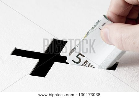 Hand of parishioner is inserting five euros into hole for donations in form of Christian cross on white background. Idea of donations for church and good deeds