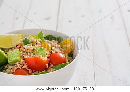 Quinoa, tomatoes and spinach on white wooden table