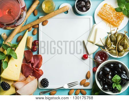 Summer wine snack set. Glass of rose, meat, cheese, olives, honey, bread sticks, nuts, capers and berries with white ceramic board in center, blue wooden background, top view, copy space