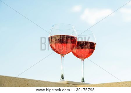 Two glasseses of rose wine, blue sky background