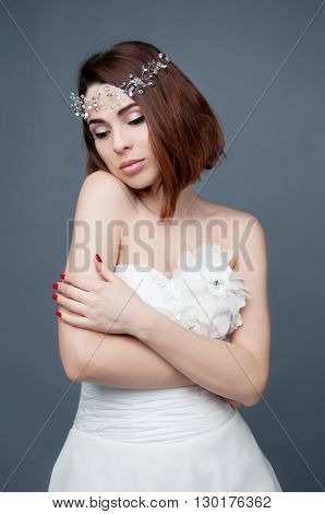 Elegant bride with brown short hair and bare shoulders white wedding dress and beaded headpiece in her hair