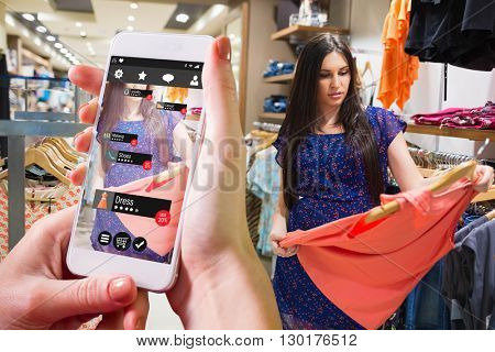Hand holding smartphone against woman standing in a shop