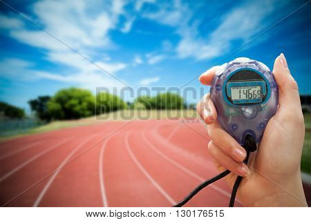 Close up of a hand holding a timer on a white background against high angle view of track