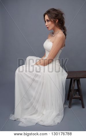 Young bride in white wedding dress sitiing on the bench. Gray backdrop.