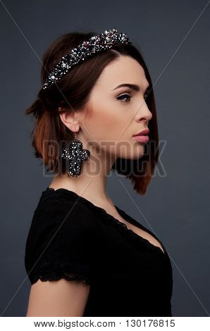 Sexy brunette in black dress with deep cleavage wearing beded crown headpiece and earrings