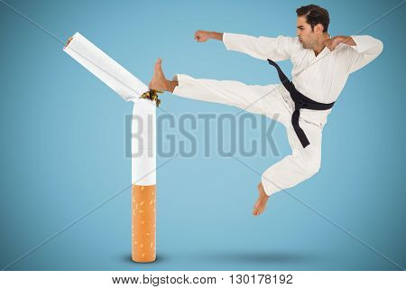 Fighter performing karate stance against blue background