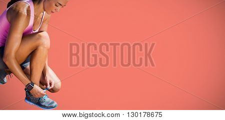 Portrait of sportswoman lacing her shoes against orange