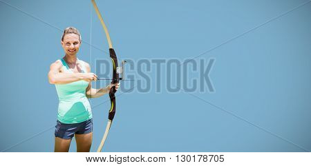Portrait of happy sportswoman posing with a bow against blue background