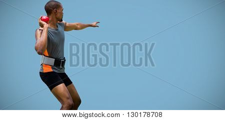 Rear view of sportsman practising shot put against blue background
