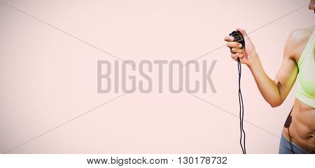 Portrait of sportswoman holding a timer against beige background