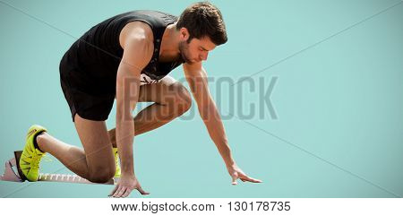 Portrait of sportsman waiting on the starting line against blue background