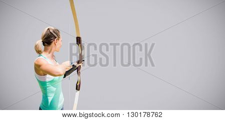 Rear view of sportswoman practising archery against light grey