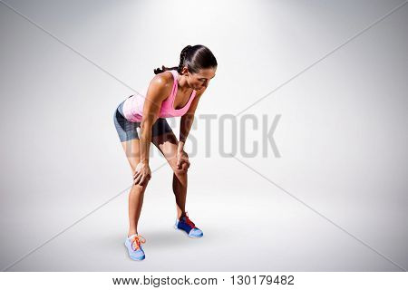 Athletic woman resting with hands on knees against grey background