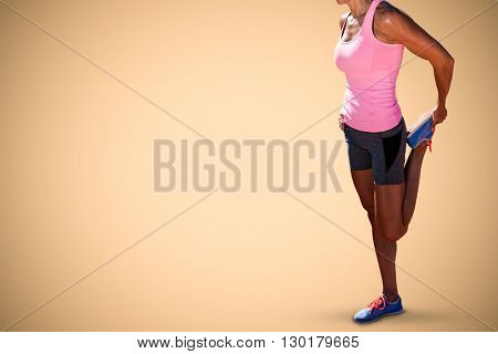 Sporty woman stretching her leg against orange background