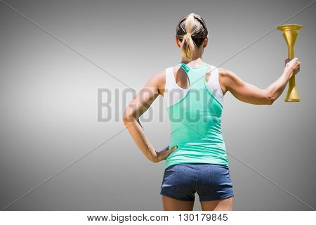 Rear view of sporty woman holding Olympic torch against grey background