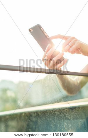 Woman touch on the cellphone under sunlight