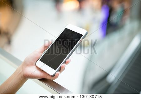 Woman hold with mobile phone inside shopping mall