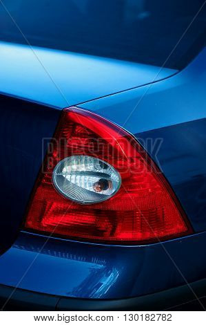 Red tail light on blue car. Detail