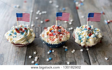 Cupcakes with American Flags for the 4th of July on wooden surface