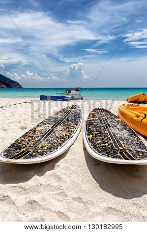 Stand up paddle boards lying on a tropical beach