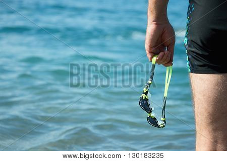 Swimmer with swimming goggles in hand at the entrance to the sea