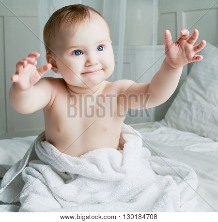 six months old baby with a towel after taking a bath, in bed at home