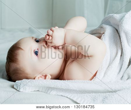 six months old baby with a towel in bed at home