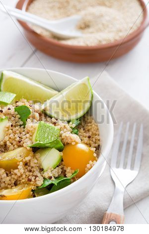 Quinoa, zucchini, tomatoes and spinach on white wooden table