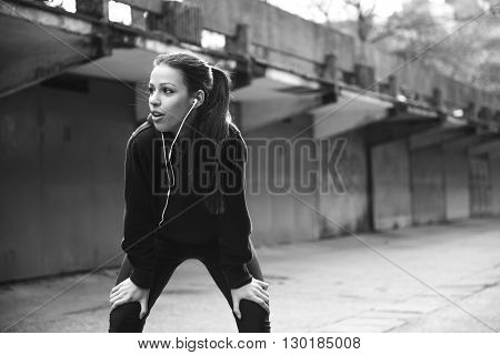 Young woman taking a breather while out for a run.