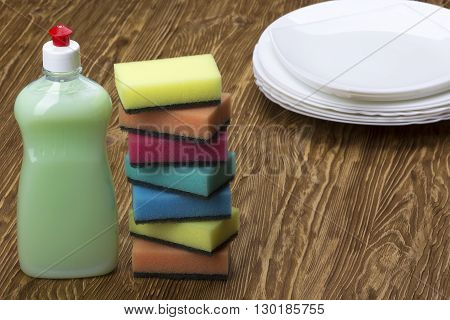 sponges, dishes and a bottle of detergent on wooden background