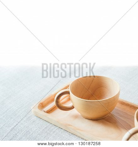 Wooden cup and saucer on grey textile with white copy space