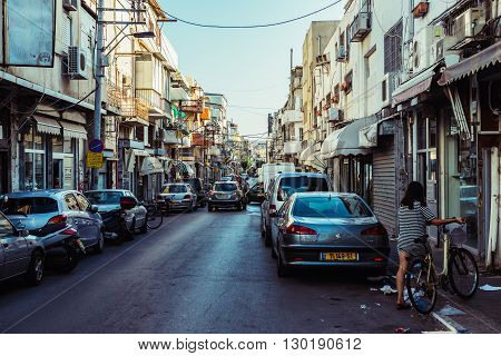 TEL AVIV ISRAEL - OCTOBER 21 2015. Woman with a bike on the street in Florentin district in Tel Aviv